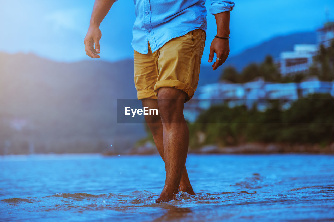 Low section of man standing in sea