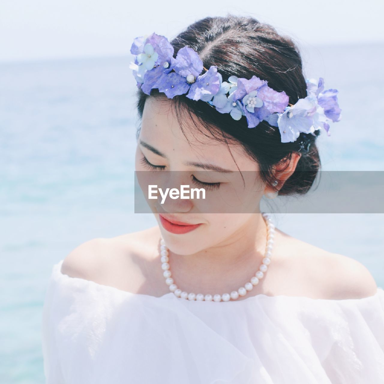 Close-Up Of Young Woman Wearing Artificial Flowers Against Sea