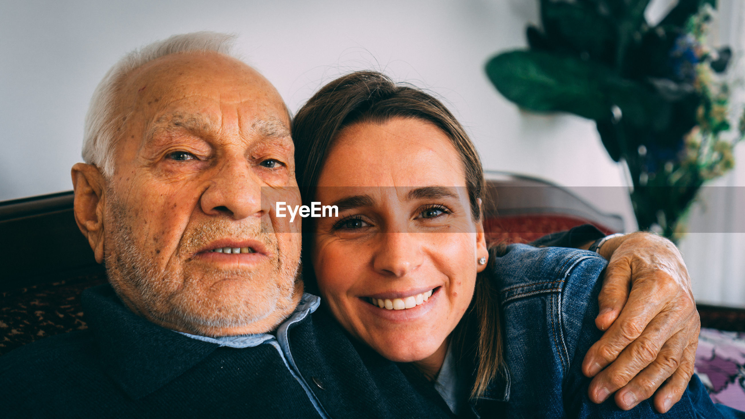 Portrait of grandfather with arm around granddaughter while sitting on sofa at home