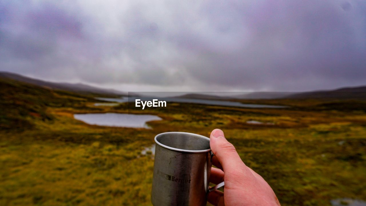 Cropped Hand Of Man Holding Cup Against Landscape