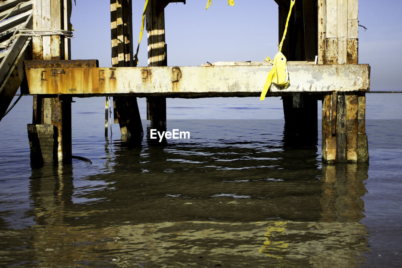 wood - material, water, pier, outdoors, day, wooden post, no people, reflection, sea, waterfront, yellow, nature, scenics, beauty in nature, horizon over water, sky