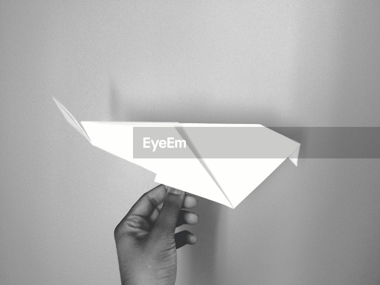 Close-Up Of Hand Holding Paper Airplane