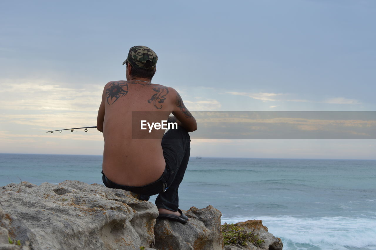 Rear view of shirtless man fishing while sitting on rock by sea