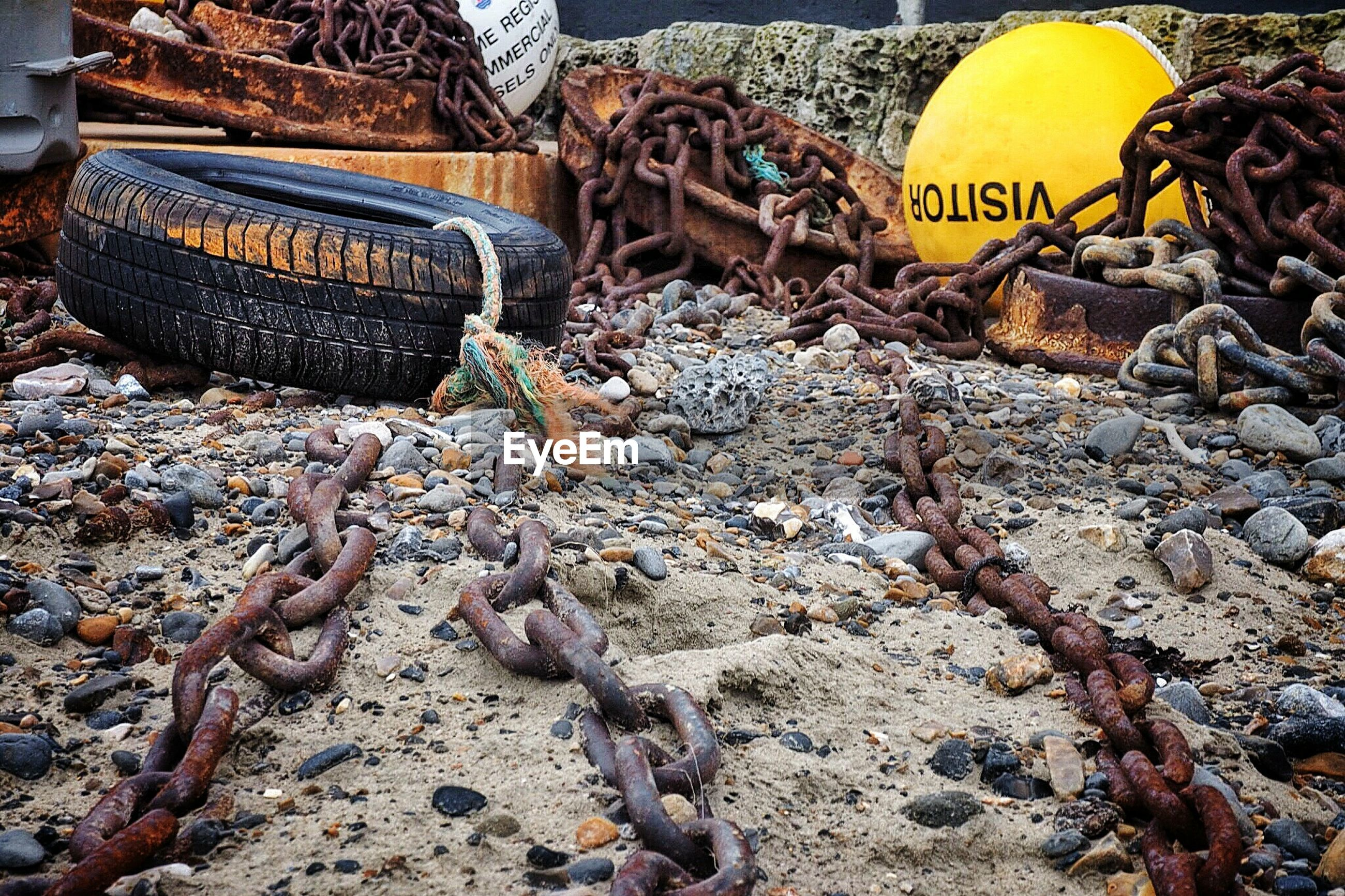 Rusty chains and tires with buoys at beach
