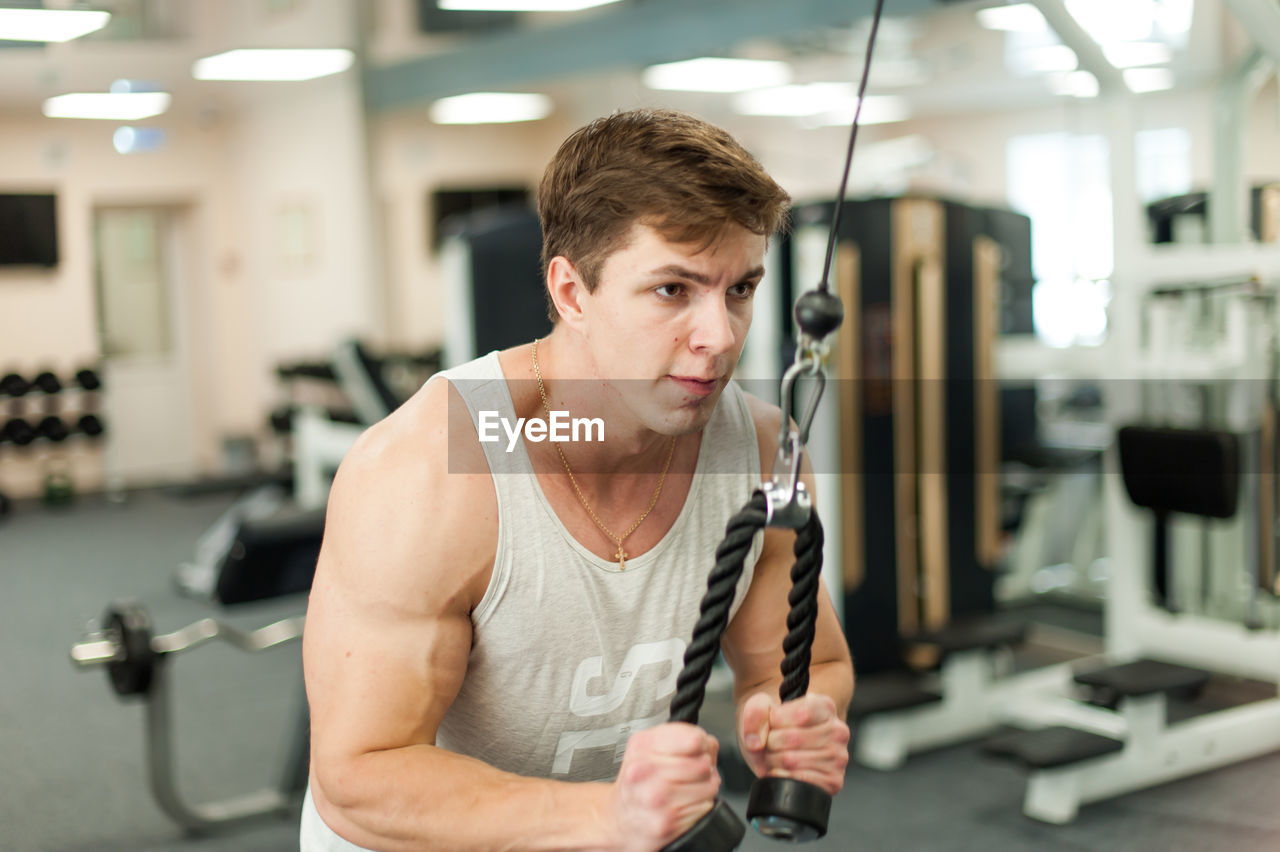 Young Man Exercising In Gym