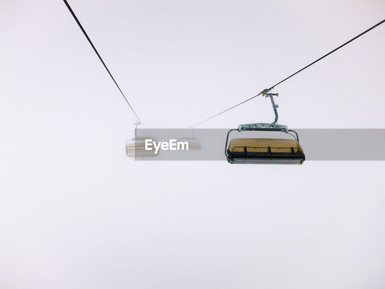 Low Angle View Ski Lifts In Foggy Weather Against Clear Sky