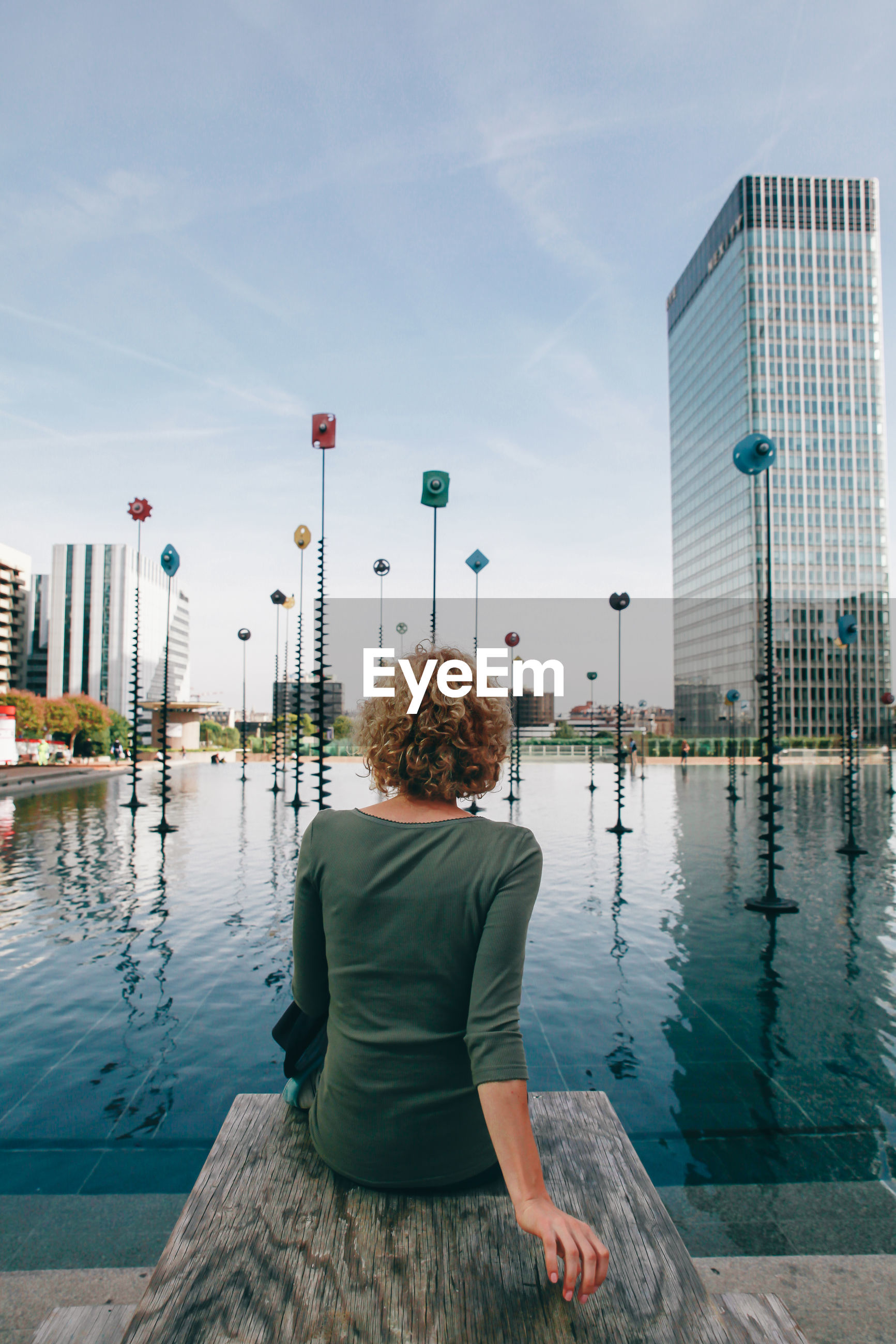 Rear view of woman sitting by lake in city against sky