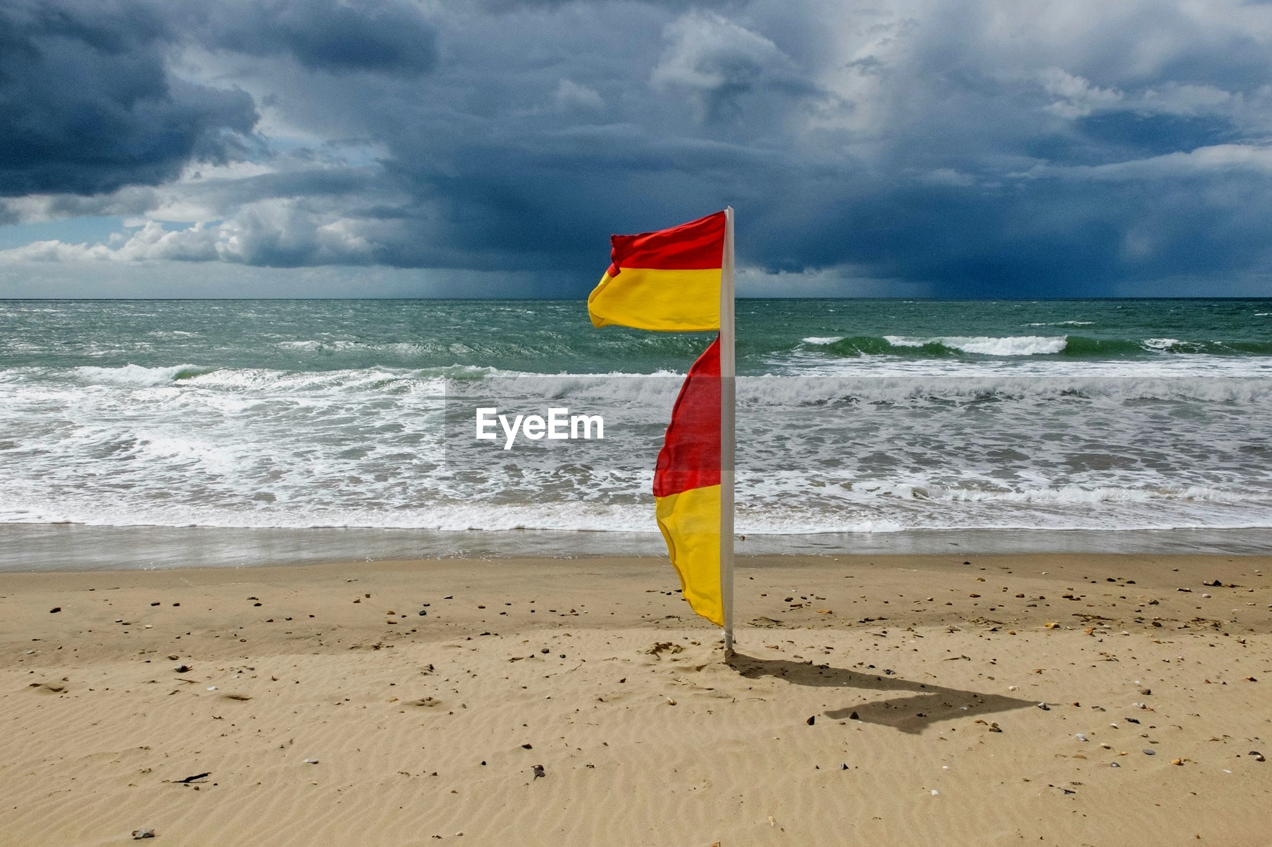 sea, horizon over water, beach, sky, water, shore, cloud - sky, tranquility, tranquil scene, scenics, sand, flag, beauty in nature, cloud, nature, cloudy, idyllic, wave, vacations, coastline