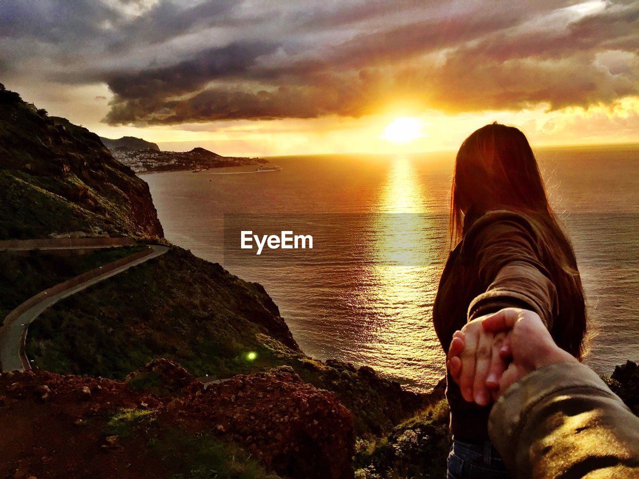 Man Holding Woman Hand On Cliff During Sunset