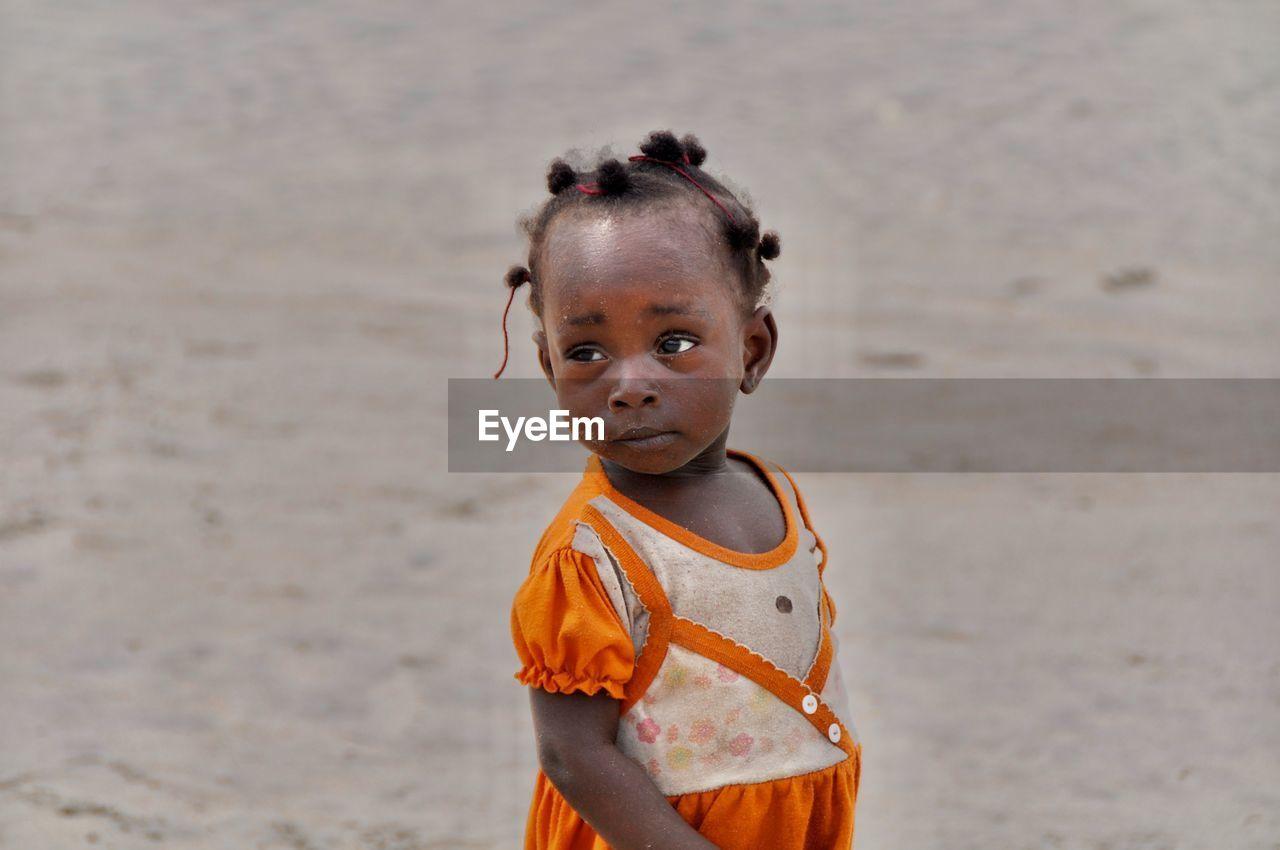Poor girl standing outdoors