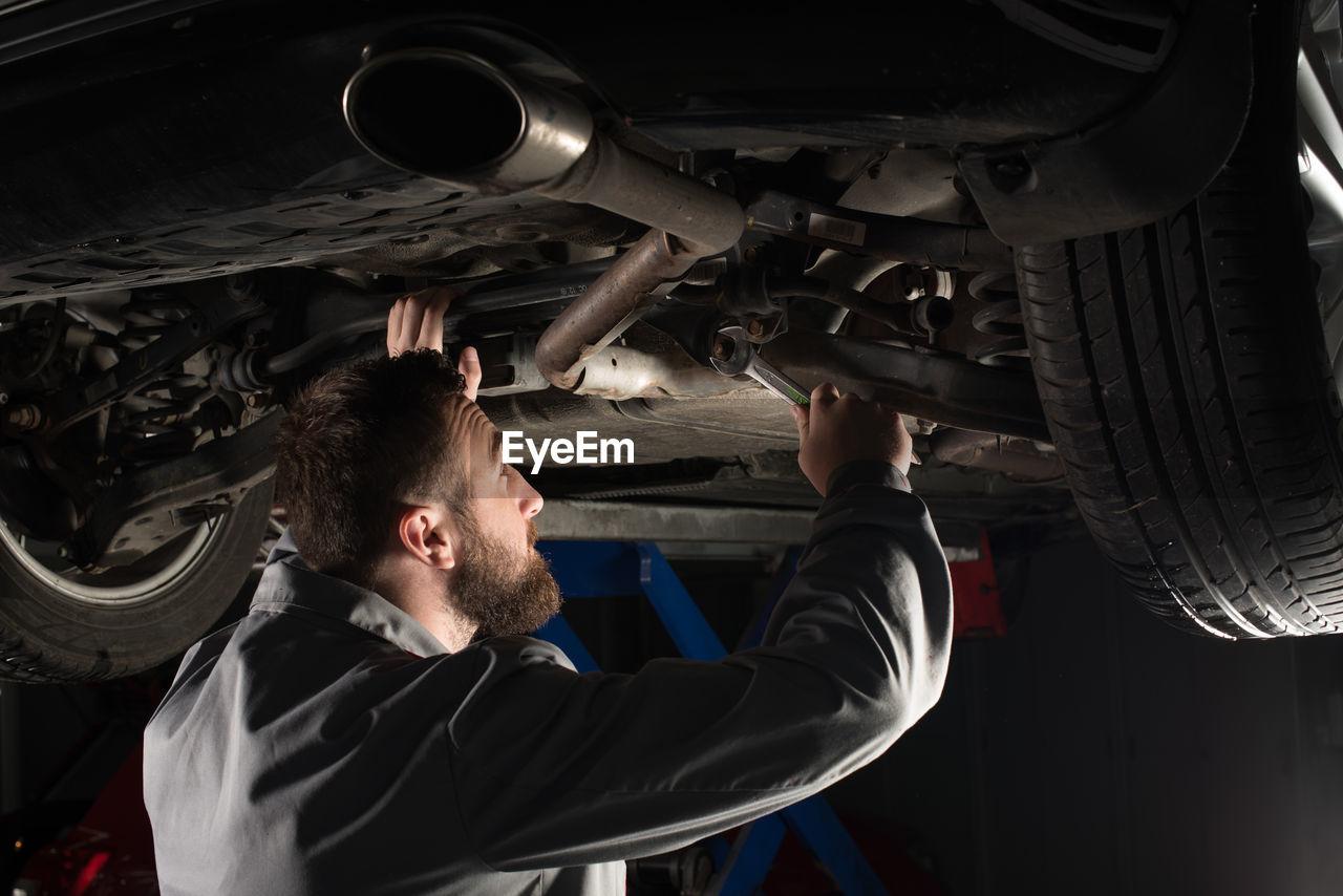 Side view of mechanic repairing car at garage