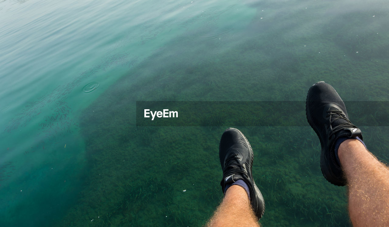 human leg, low section, water, personal perspective, shoe, high angle view, one person, real people, day, men, outdoors, human body part, nature, close-up, people