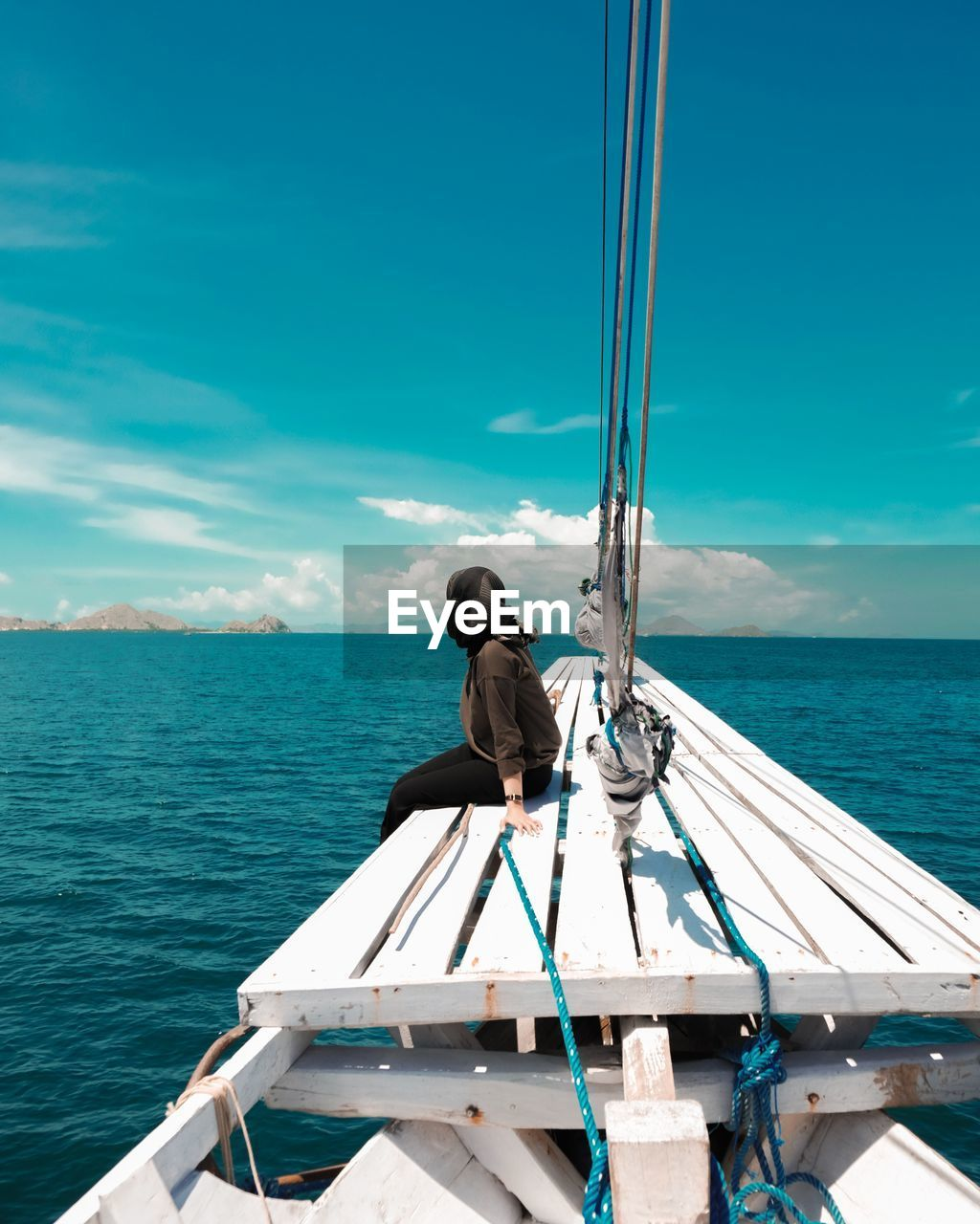 Rear view of man sitting on boat in sea against sky