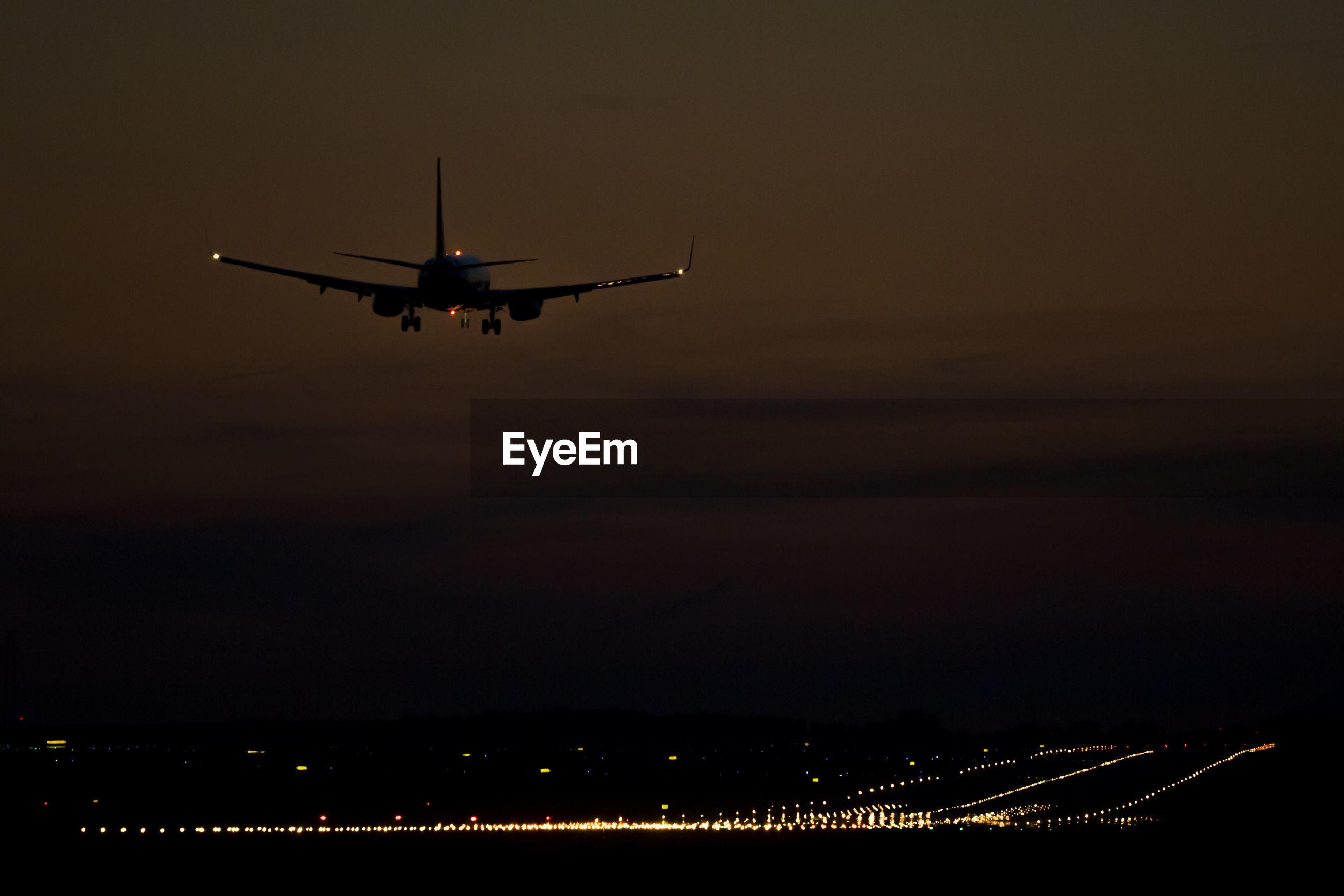 Silhouette airplane landing on illuminated runway at night