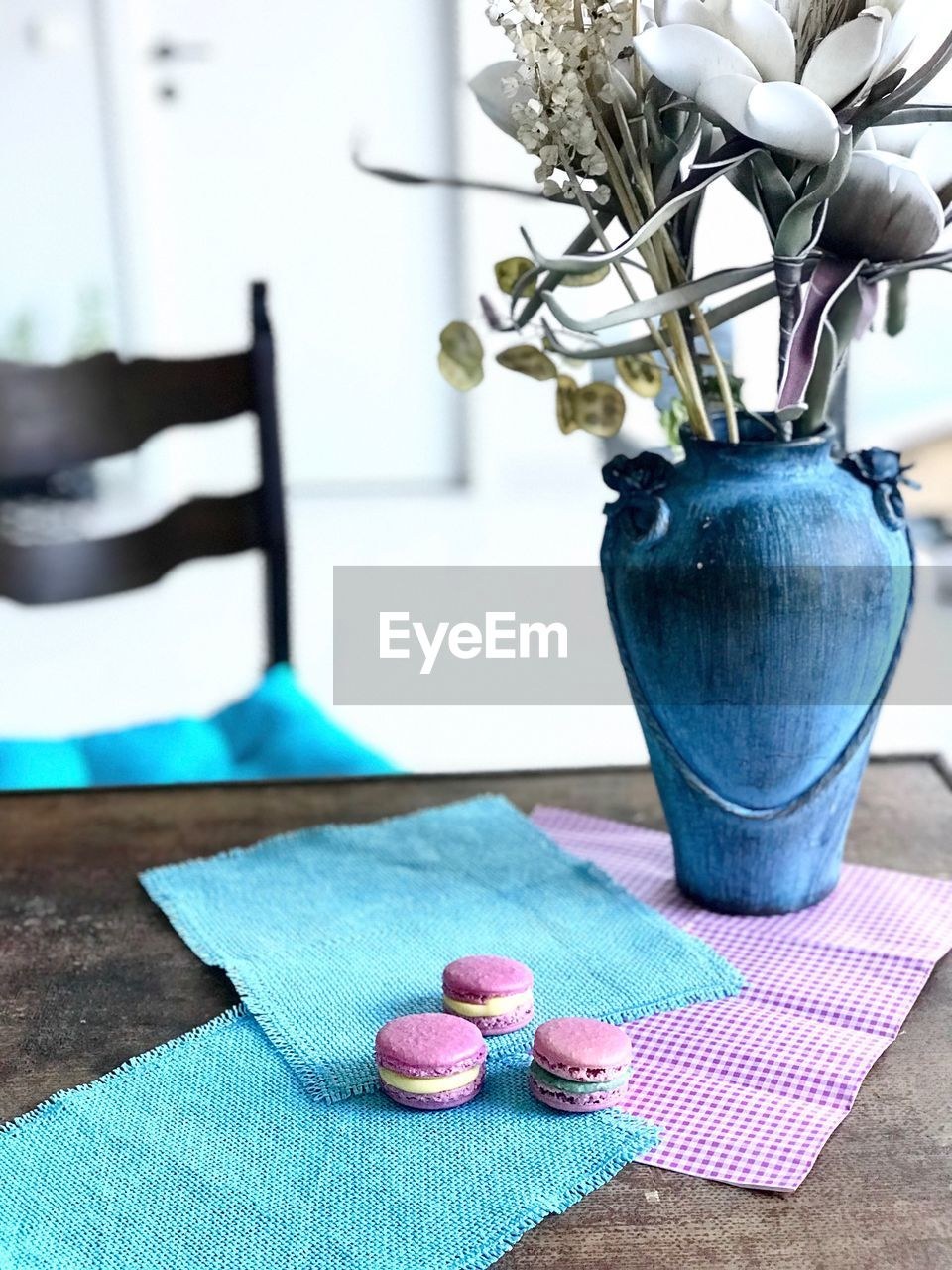 table, indoors, no people, close-up, focus on foreground, still life, plant, blue, flower, textile, flowering plant, freshness, day, nature, vase, container, selective focus, wood - material