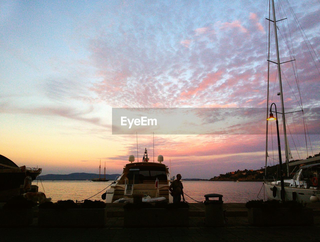 nautical vessel, sunset, sky, sea, transportation, water, cloud - sky, mode of transport, boat, nature, moored, harbor, orange color, beauty in nature, scenics, outdoors, mast, built structure, tranquility, tranquil scene, travel destinations, yacht, travel, ship, no people, silhouette, architecture, sailboat, building exterior, horizon over water, sailing, sailing ship, day