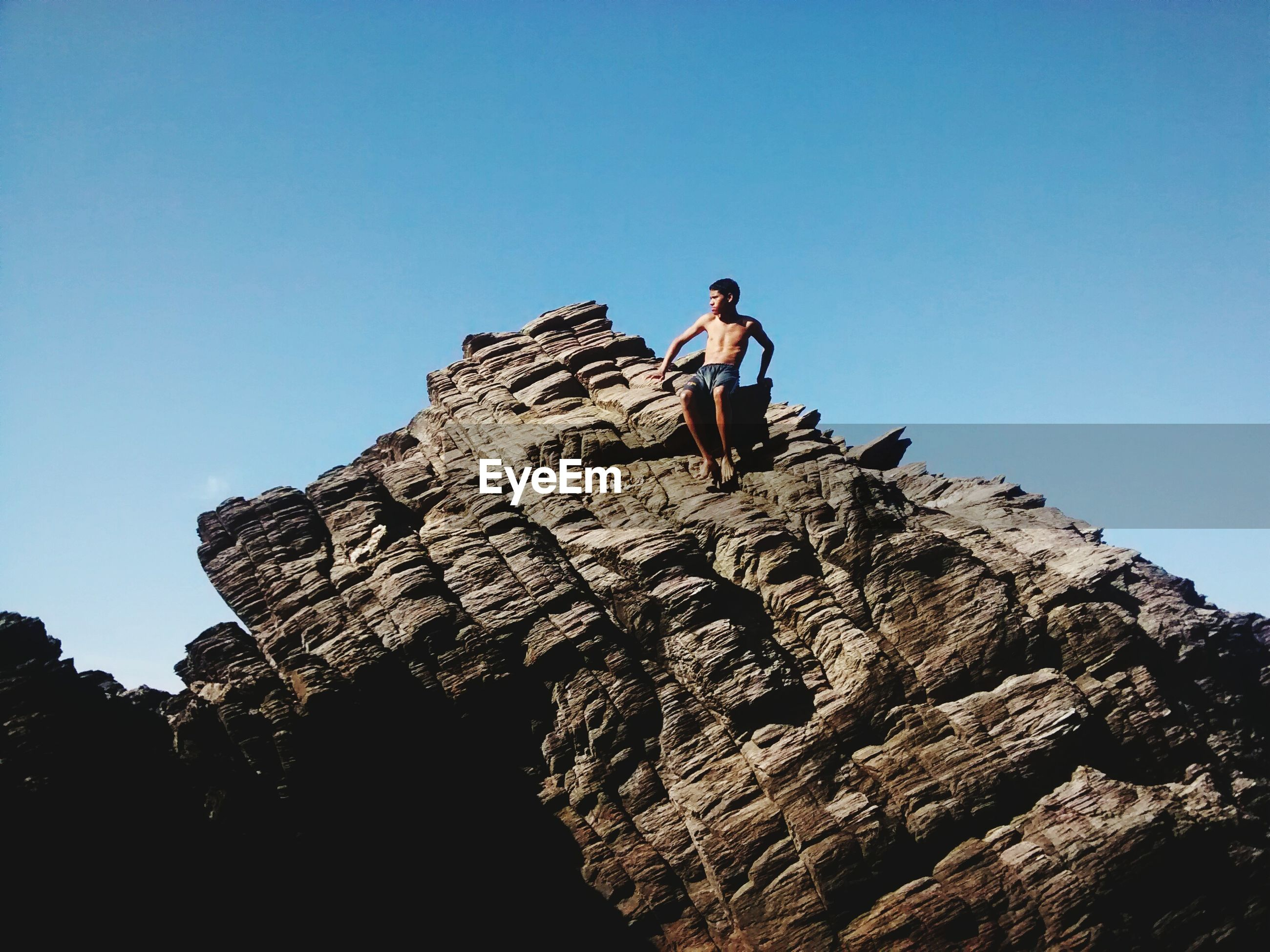 Low angle view of shirtless boy sitting on rock formation against clear blue sky