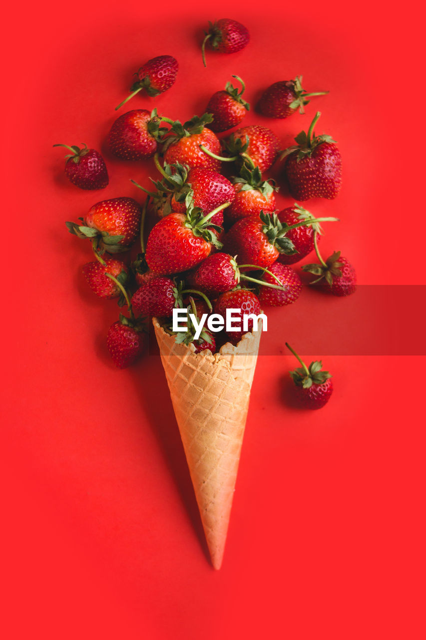 Close-Up Of Ice Cream Cone With Strawberries Against Red Background