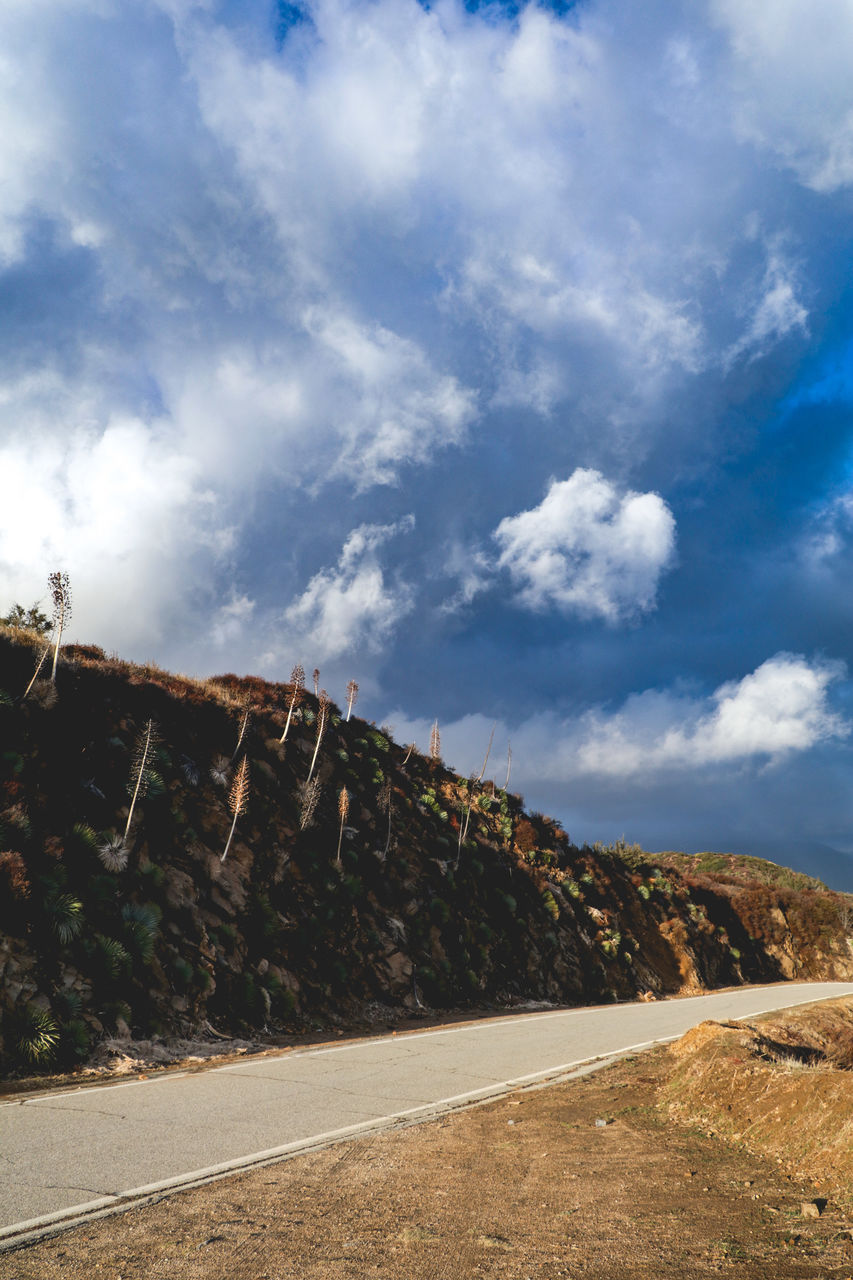sky, cloud - sky, mountain, nature, day, road, beauty in nature, scenics - nature, transportation, tranquility, no people, tranquil scene, environment, non-urban scene, rock, landscape, outdoors, land, sunlight, rock formation