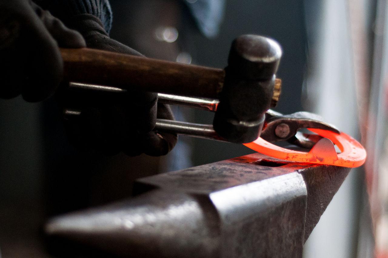 Cropped Image Of Farrier Making Horseshoe