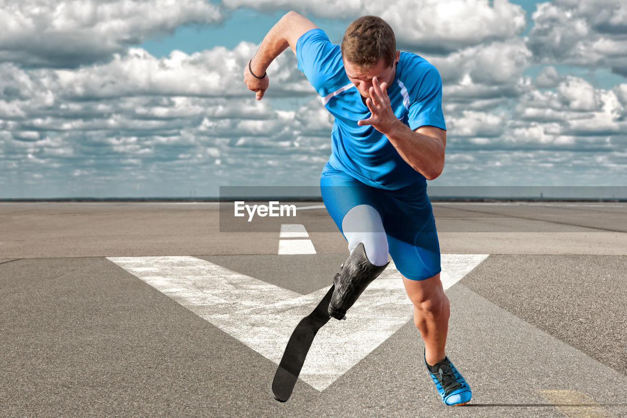 Disabled man running on road against sky