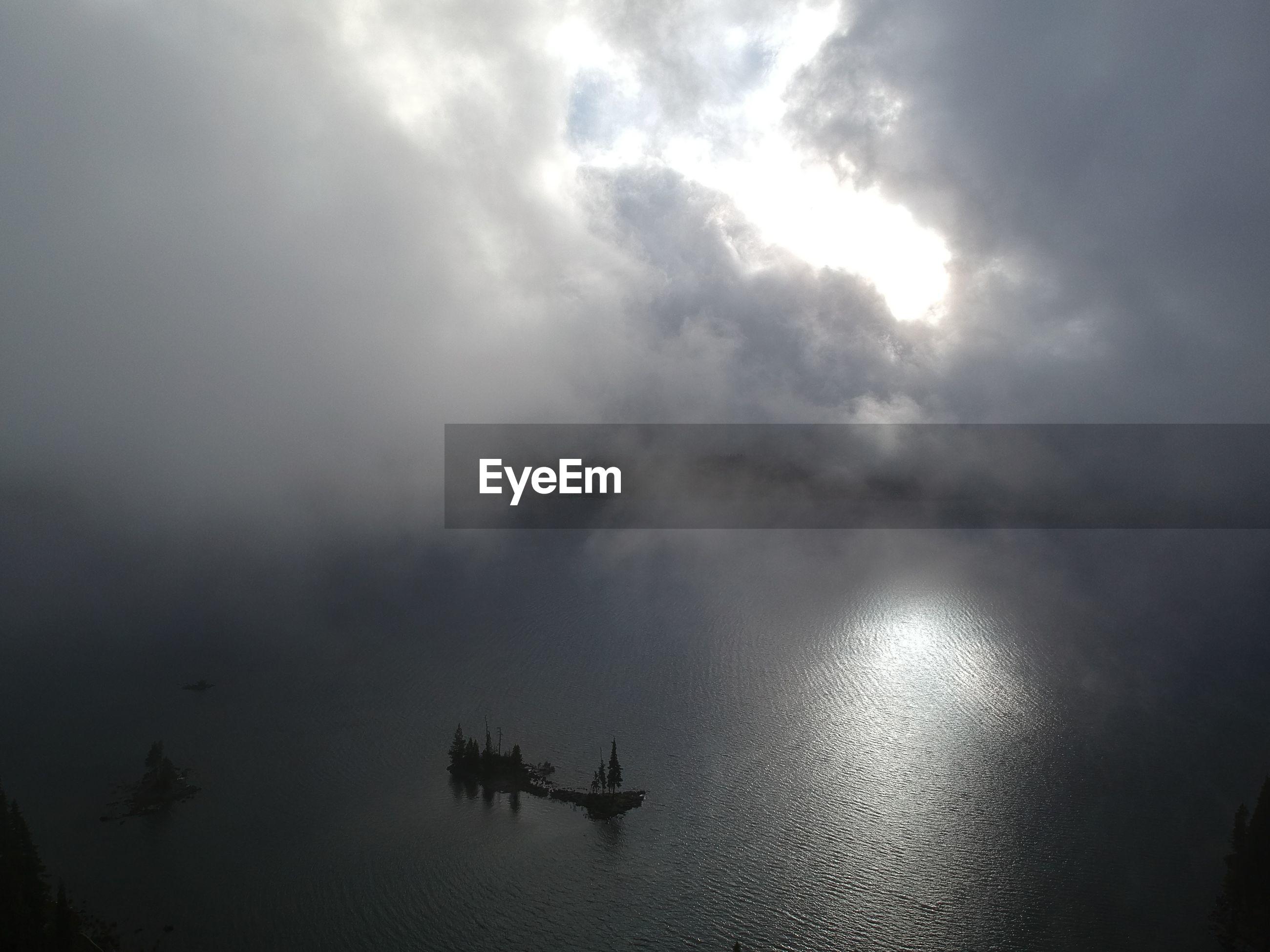 SILHOUETTE PEOPLE IN LAKE AGAINST SKY