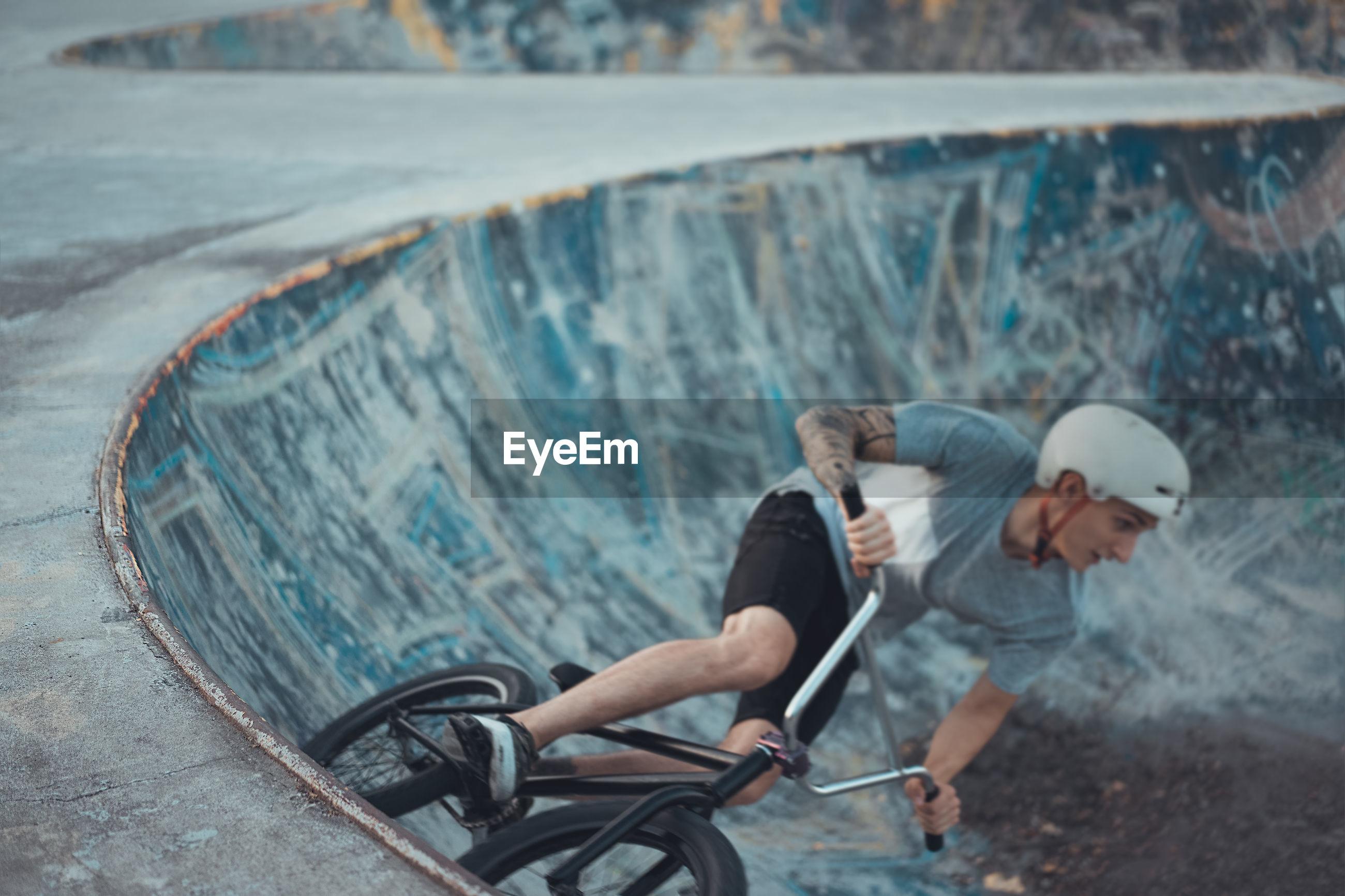 Man cycling on sports ramp