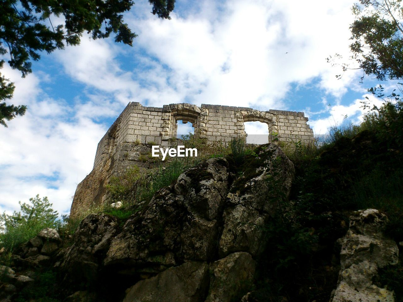 low angle view, cloud - sky, history, sky, ancient, ancient civilization, tree, day, architecture, archaeology, old ruin, rock - object, built structure, nature, outdoors, no people, travel destinations