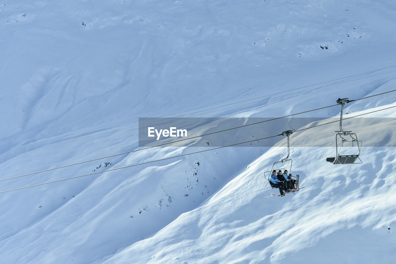 People Traveling In Ski Lift Over Snowcapped Mountain