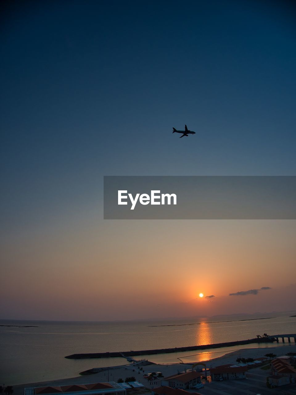 sky, flying, sunset, water, mode of transportation, air vehicle, transportation, airplane, beauty in nature, sea, mid-air, scenics - nature, nature, no people, clear sky, travel, sun, horizon, motion, outdoors, horizon over water
