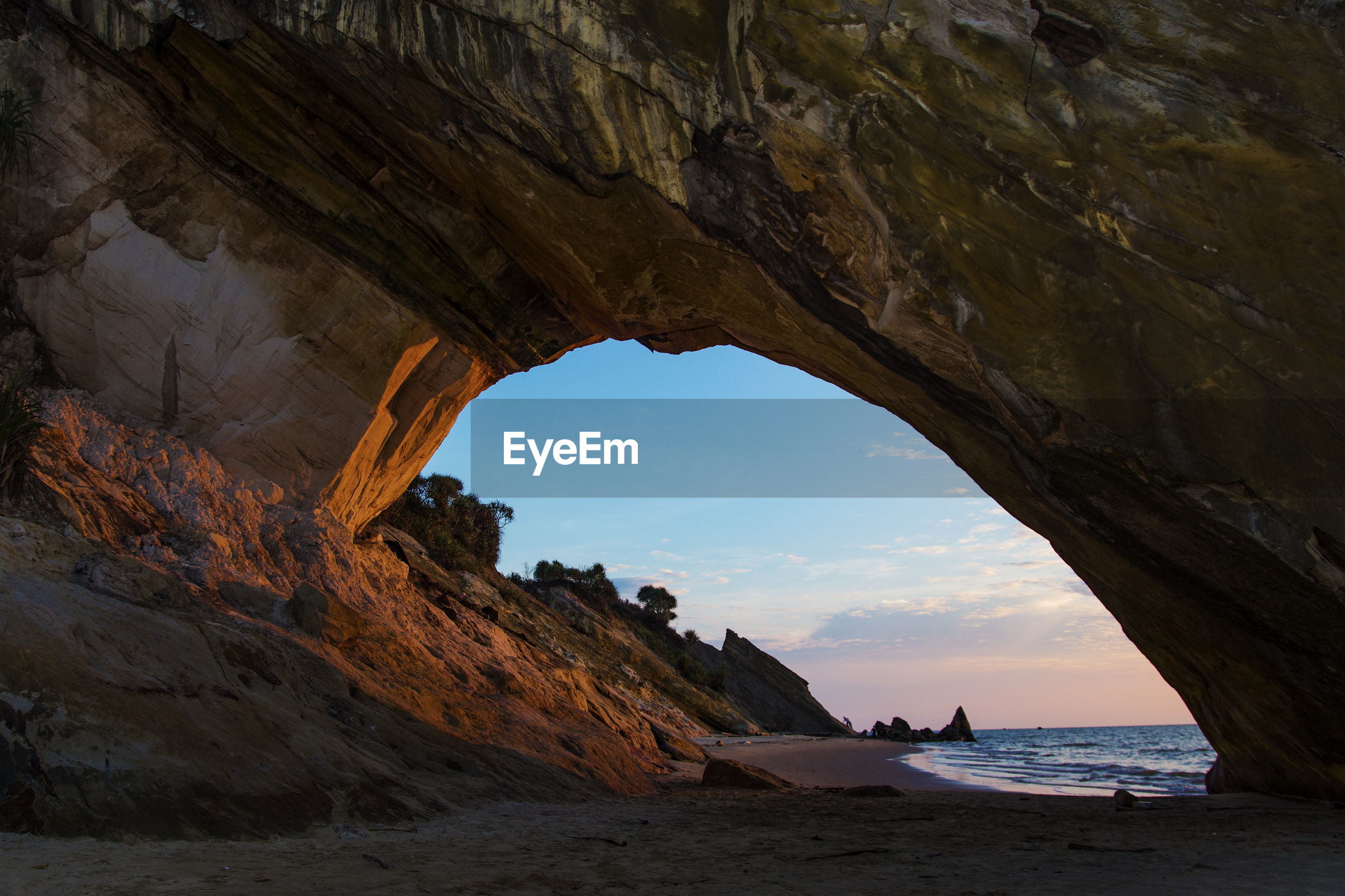 Scenic view of sea seen through cave during sunset