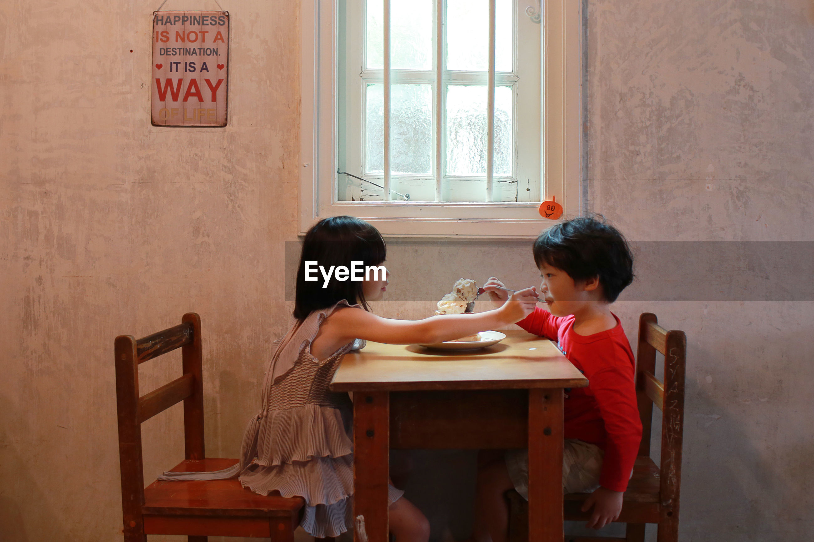 Siblings eating at table