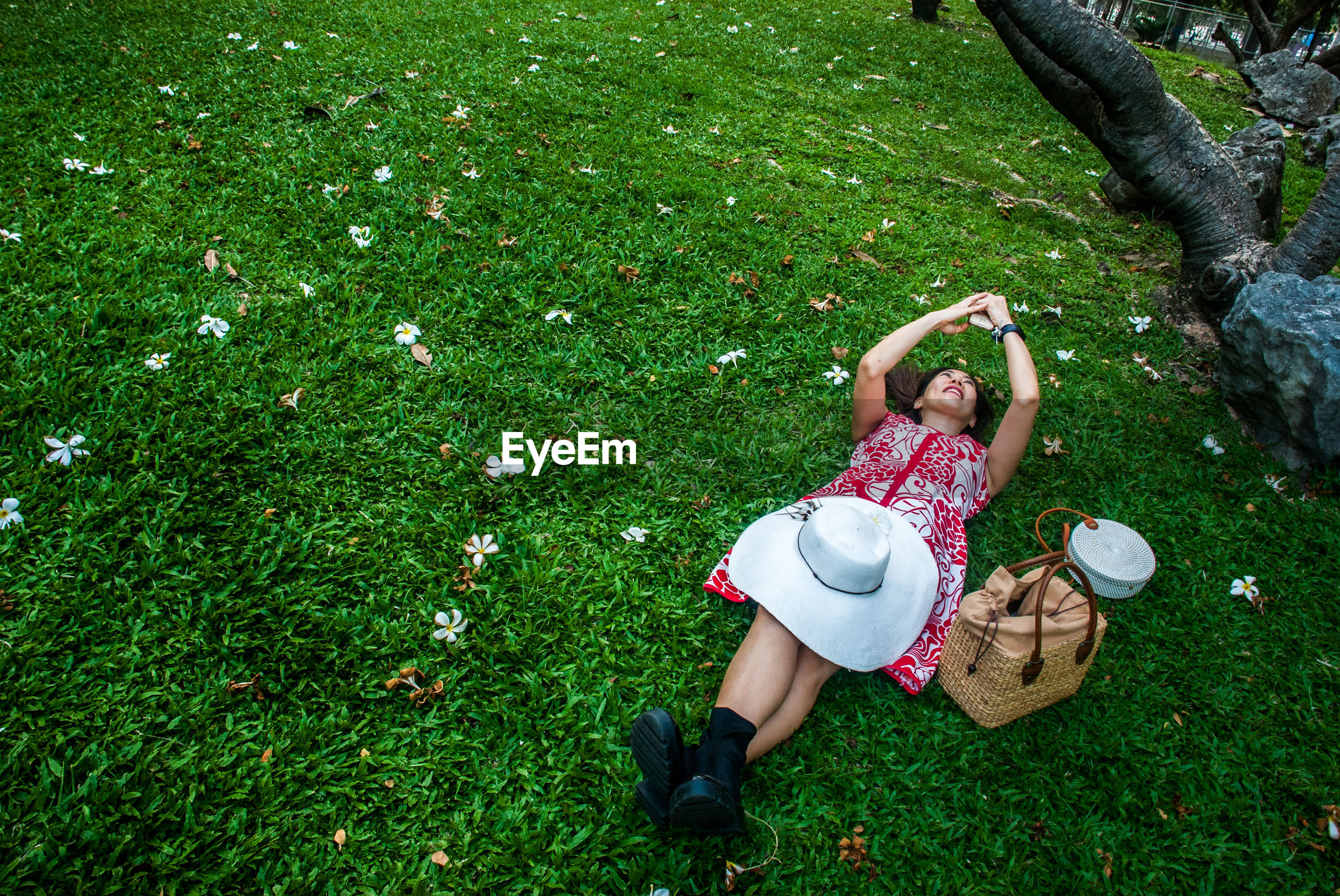 High angle view of woman using mobile phone while lying down on field