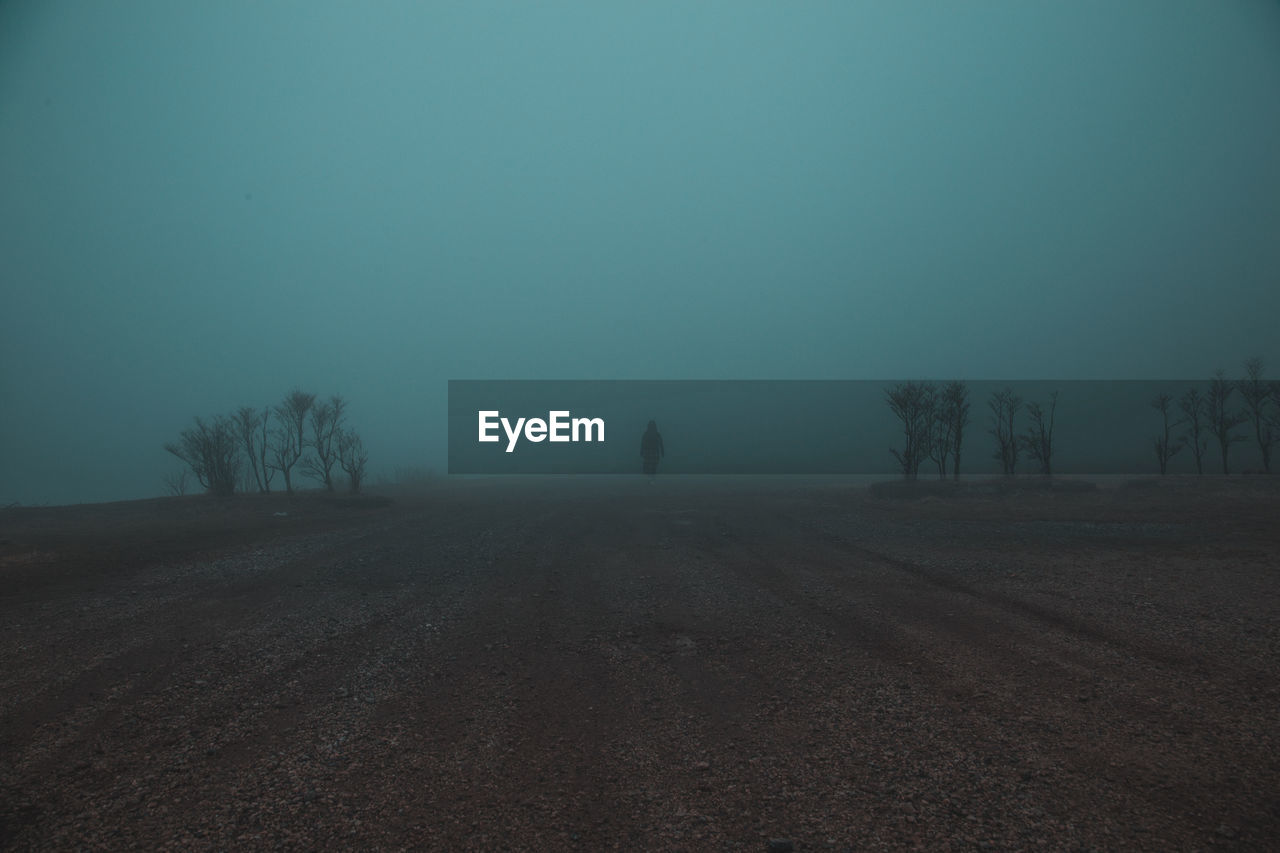 Distant View Of Woman On Field During Foggy Weather