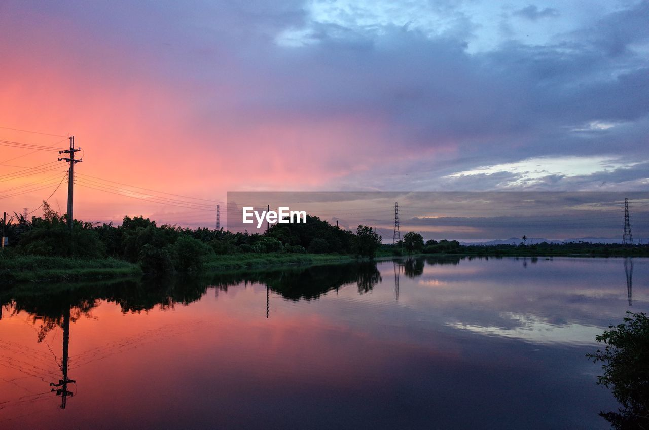 sky, reflection, sunset, water, cloud - sky, beauty in nature, scenics - nature, electricity pylon, lake, nature, waterfront, orange color, tranquility, tree, technology, tranquil scene, fuel and power generation, plant, no people, electricity, outdoors, power supply