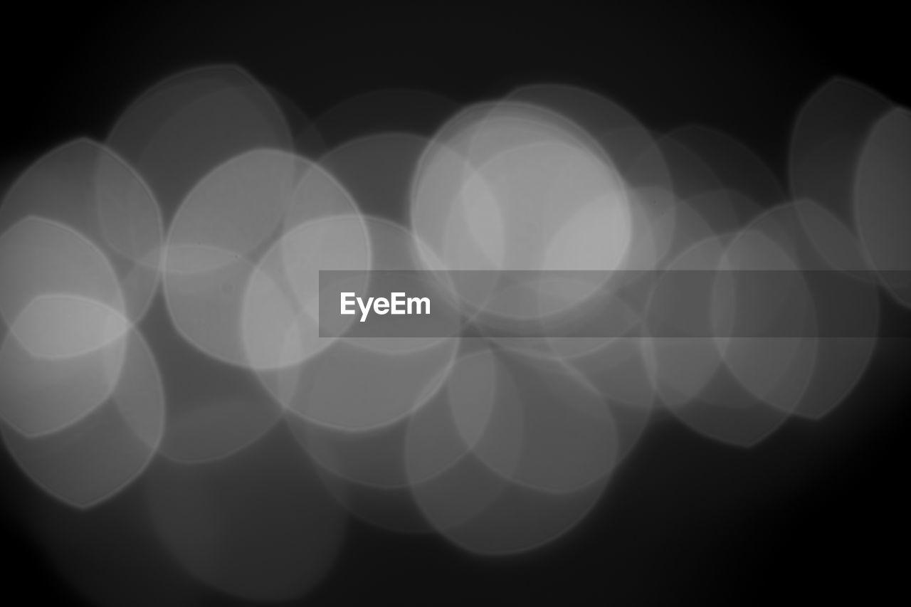 Defocused image of illuminated lights on black background