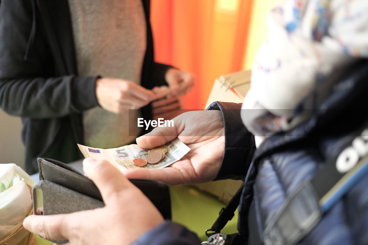 midsection, holding, real people, human hand, group of people, hand, people, selective focus, men, women, currency, lifestyles, adult, incidental people, paper currency, occupation, leisure activity, human body part