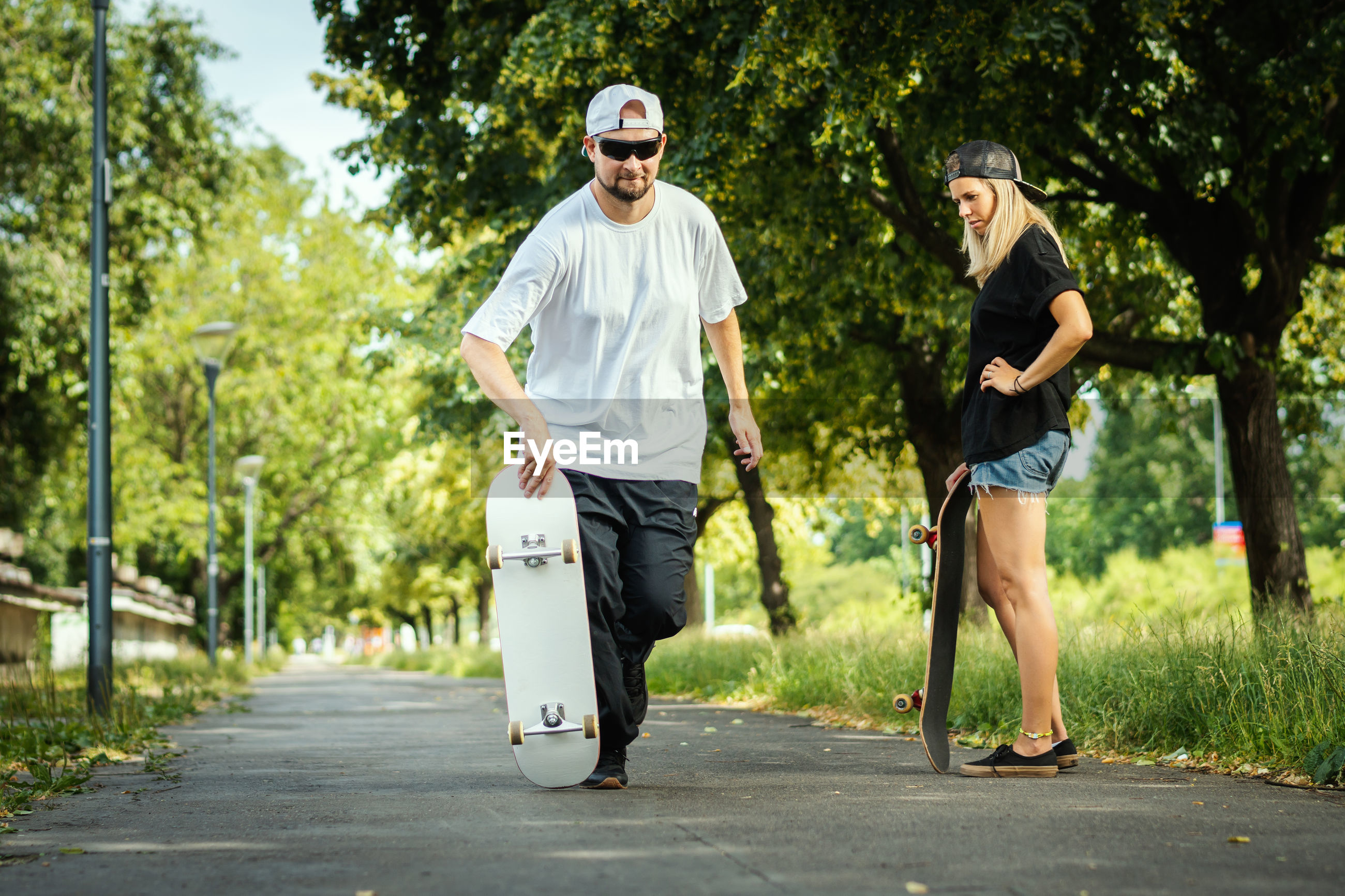 Couple with skateboards on footpath at park