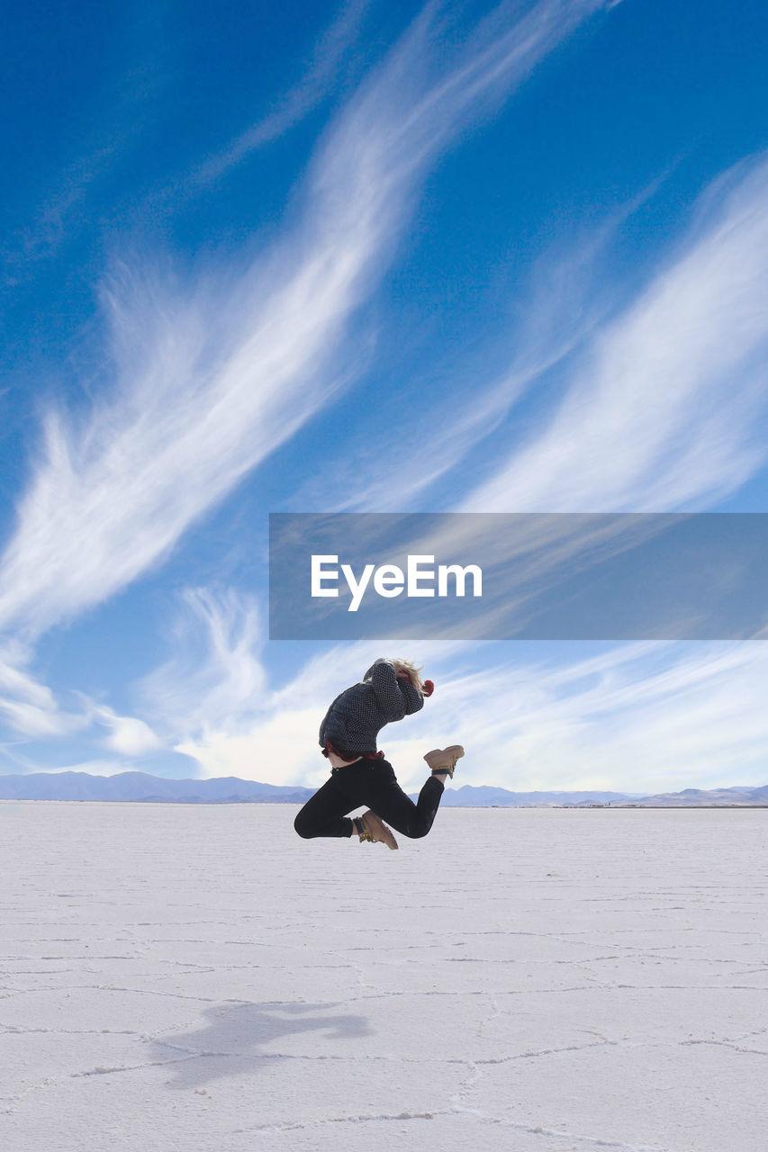 Woman jumping on salt flat against blue sky