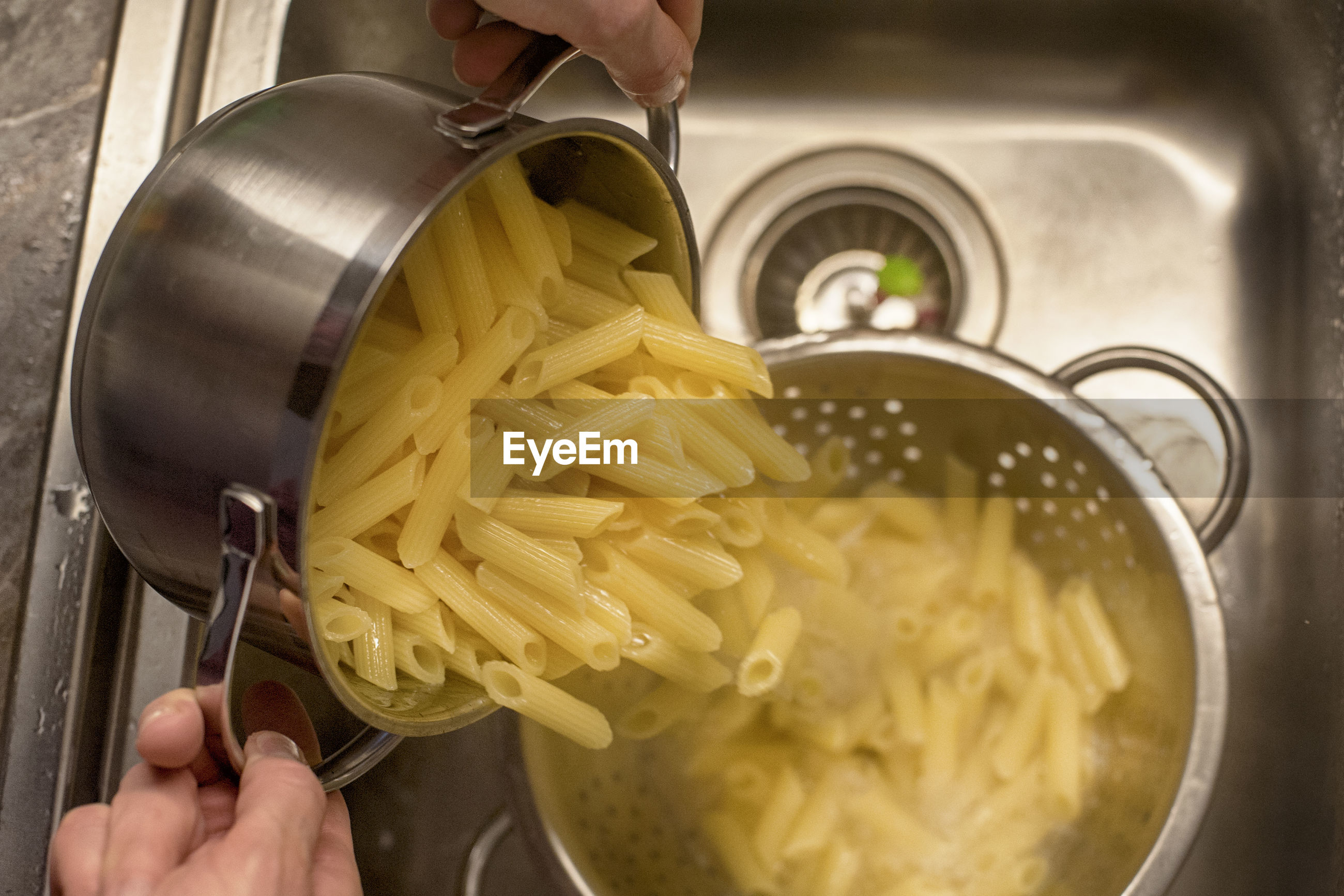 Midsection of person preparing pasta in kitchen