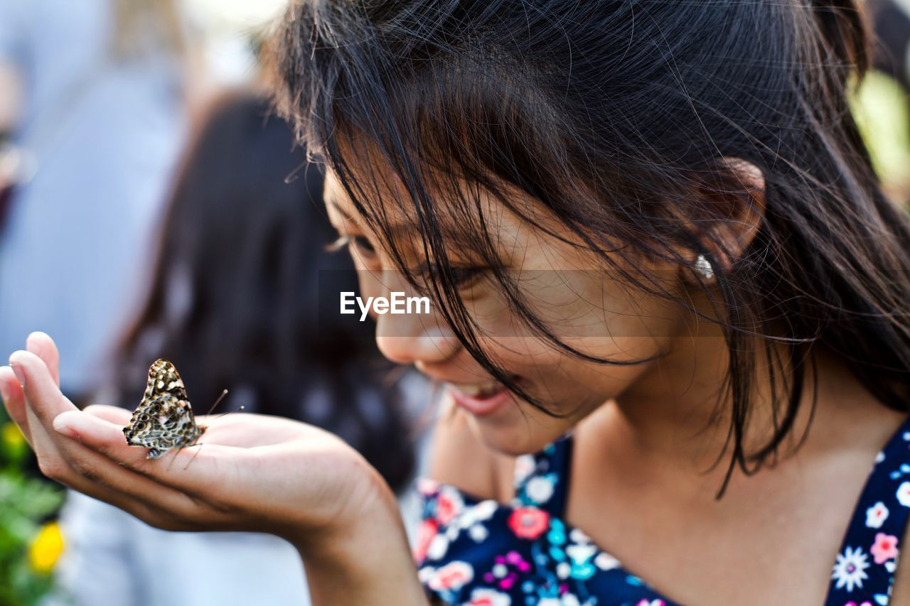Close-up of cute smiling girl looking at butterfly on hand
