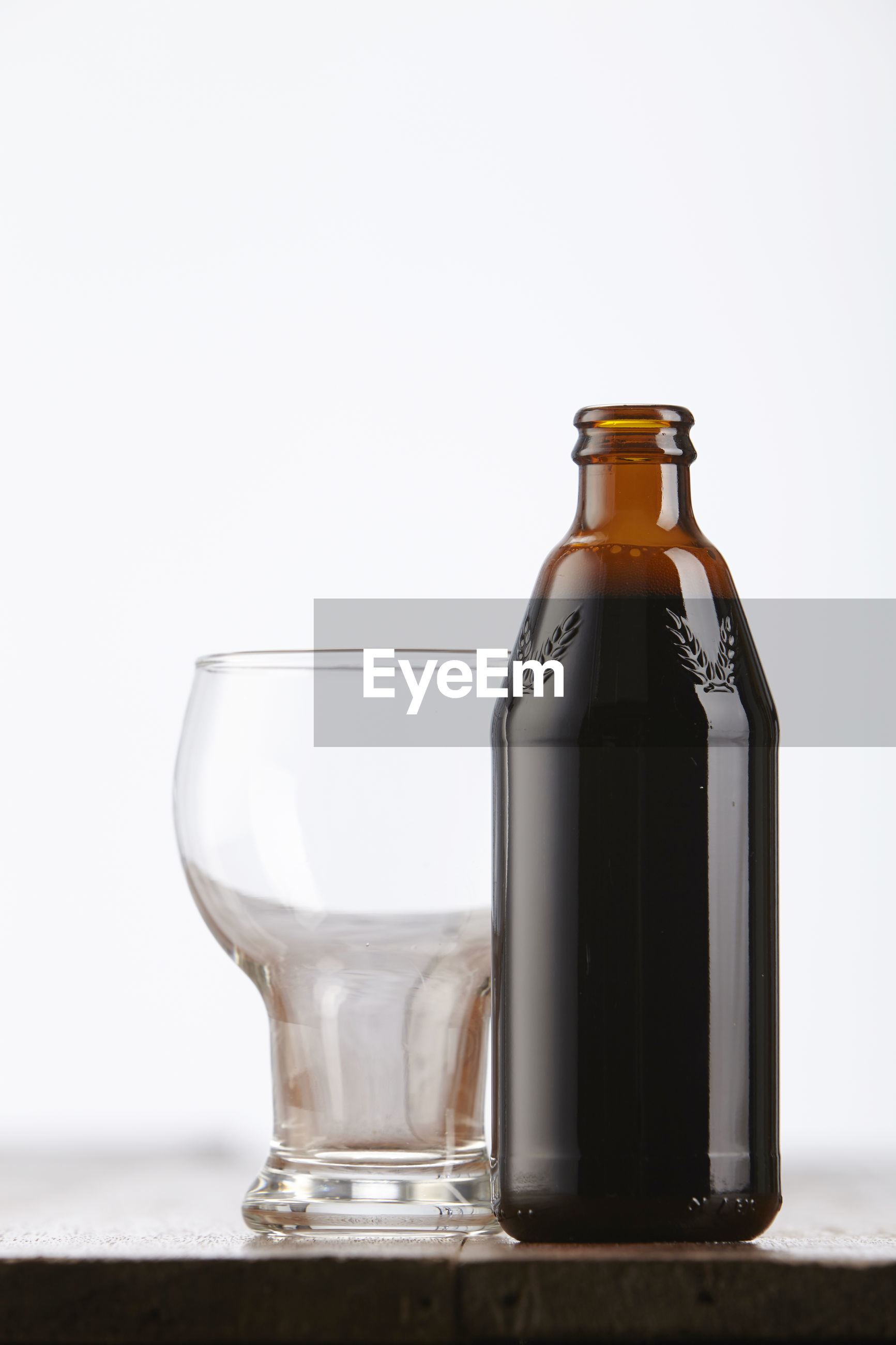 Close-up of drink in bottle by glass on table against white background