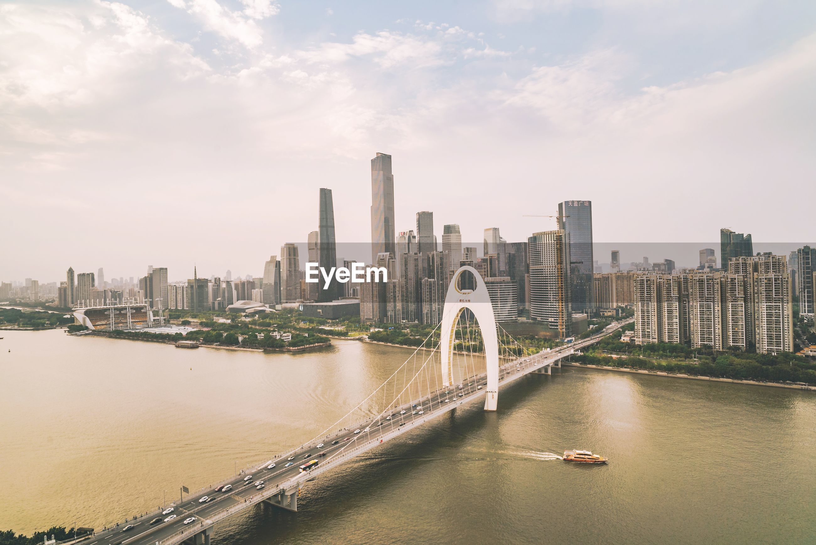 Bridge over river amidst in city against sky