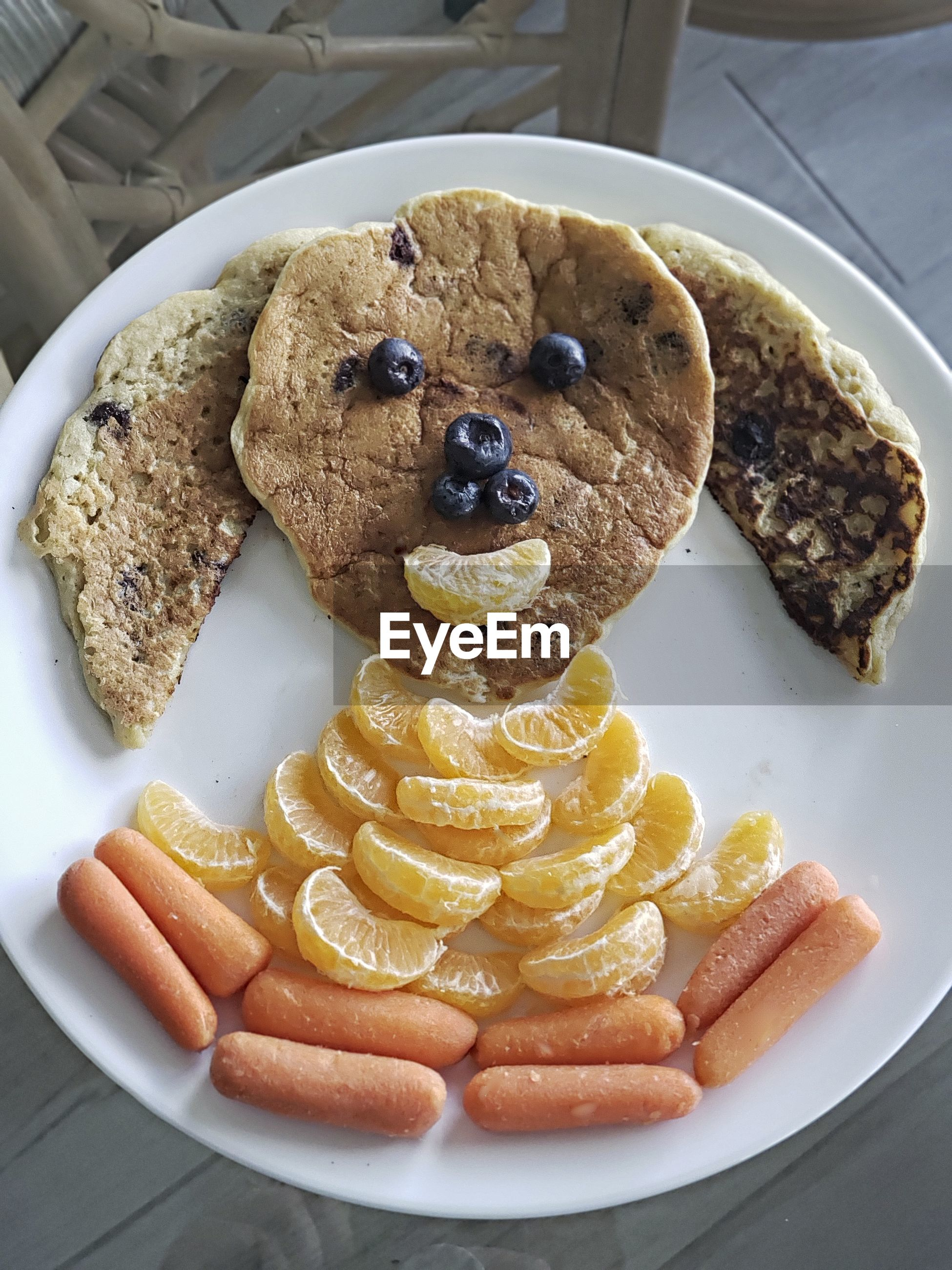 A healthy puppy pancake meal made of whole wheat pancakes, blueberries, orange slices and carrots,