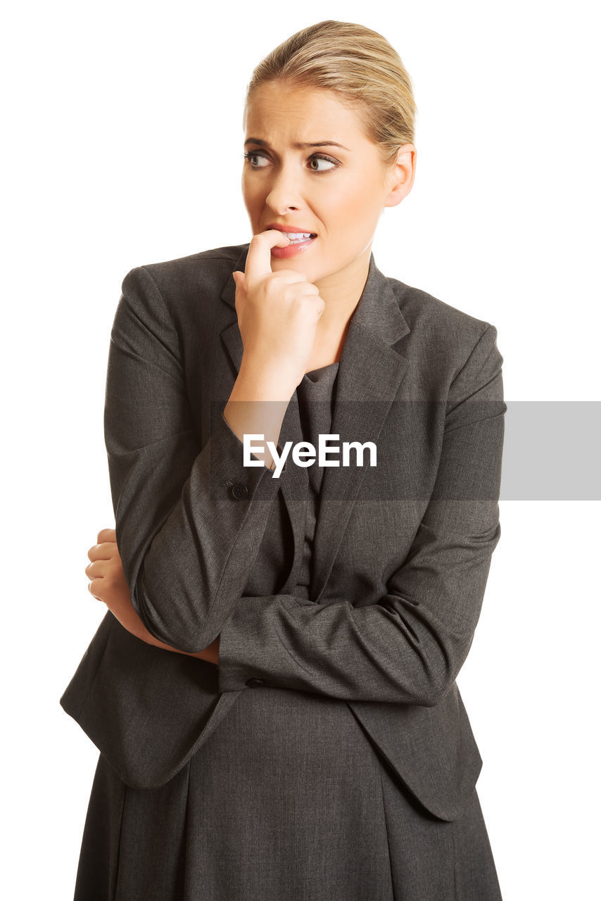 Businesswoman looking away while standing against white background