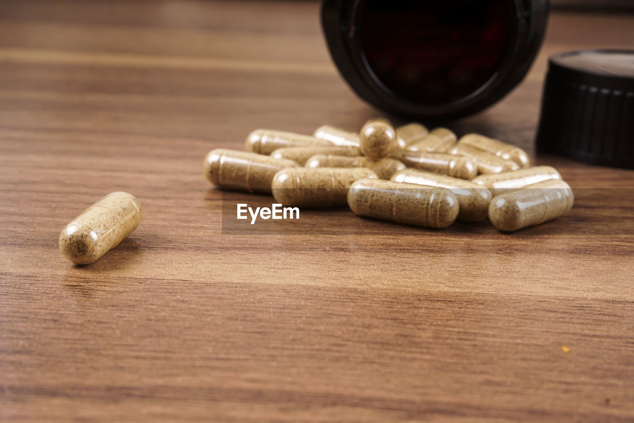 table, wood - material, still life, indoors, selective focus, no people, close-up, pill, medicine, dose, capsule, food and drink, large group of objects, brown, nutritional supplement, healthcare and medicine, vitamin, ammunition, wellbeing, high angle view