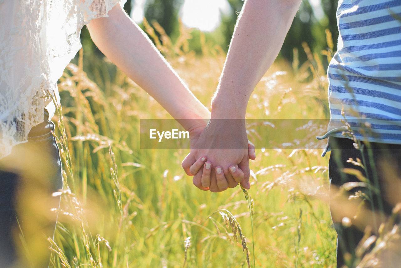Close-Up Of Couple Holding Hands On Field