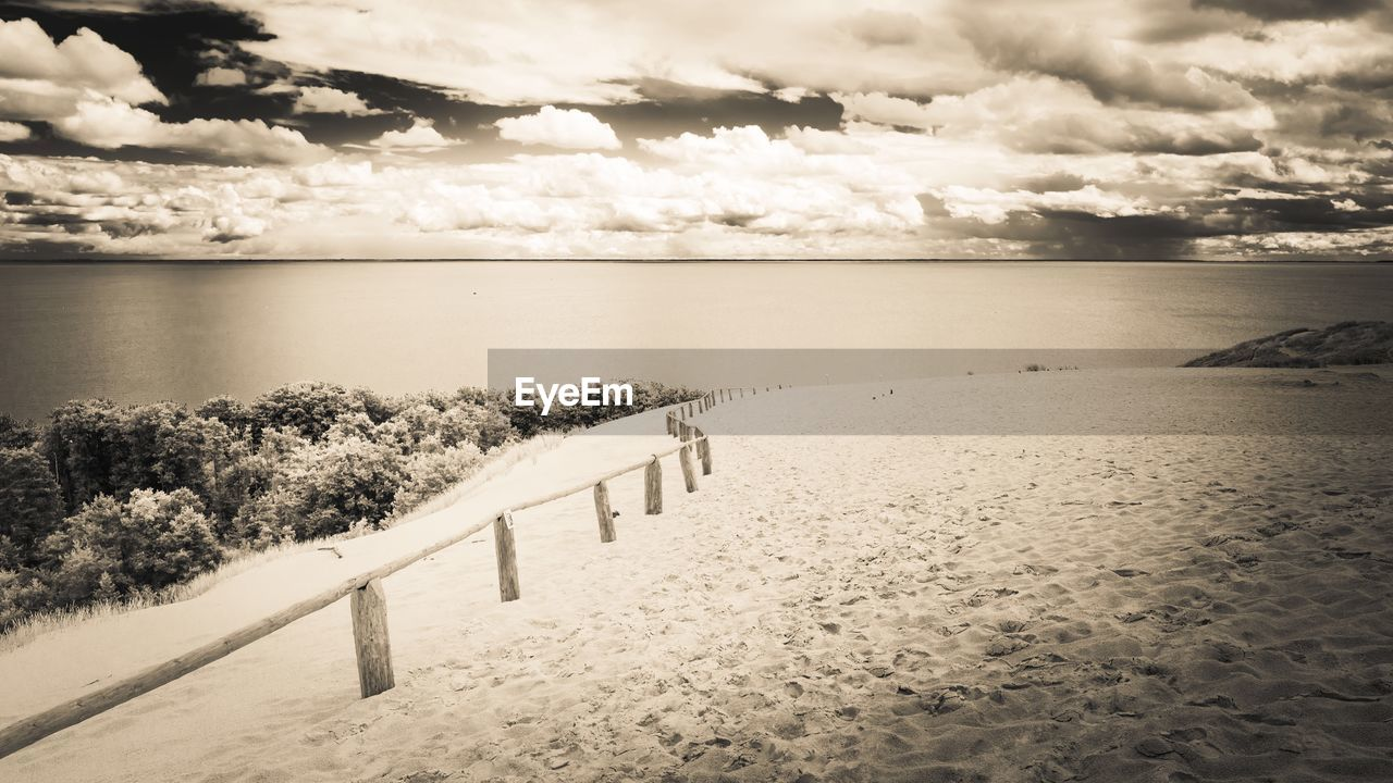 cloud - sky, sky, water, tranquil scene, tranquility, scenics - nature, beauty in nature, sea, nature, horizon, no people, land, railing, day, horizon over water, beach, outdoors, sand