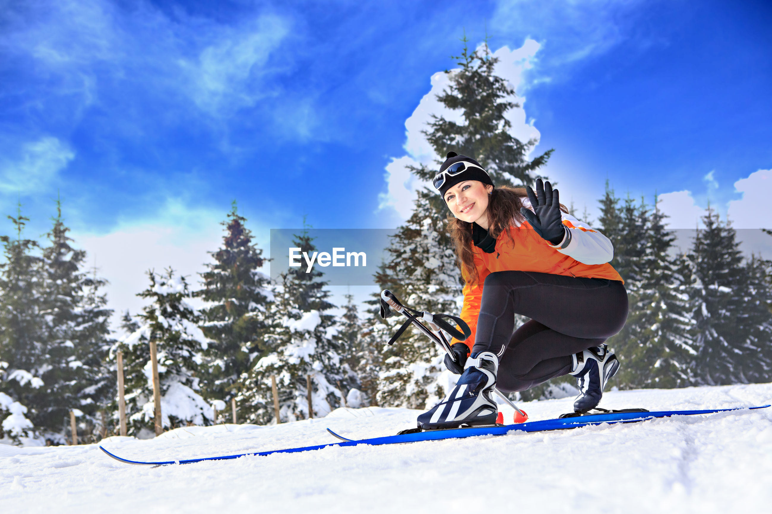 Portrait of woman wearing ski sitting on snow covered field