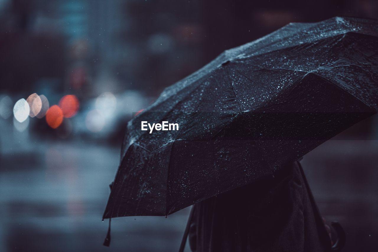 Close-Up Of Person Carrying Umbrella During Rainy Season